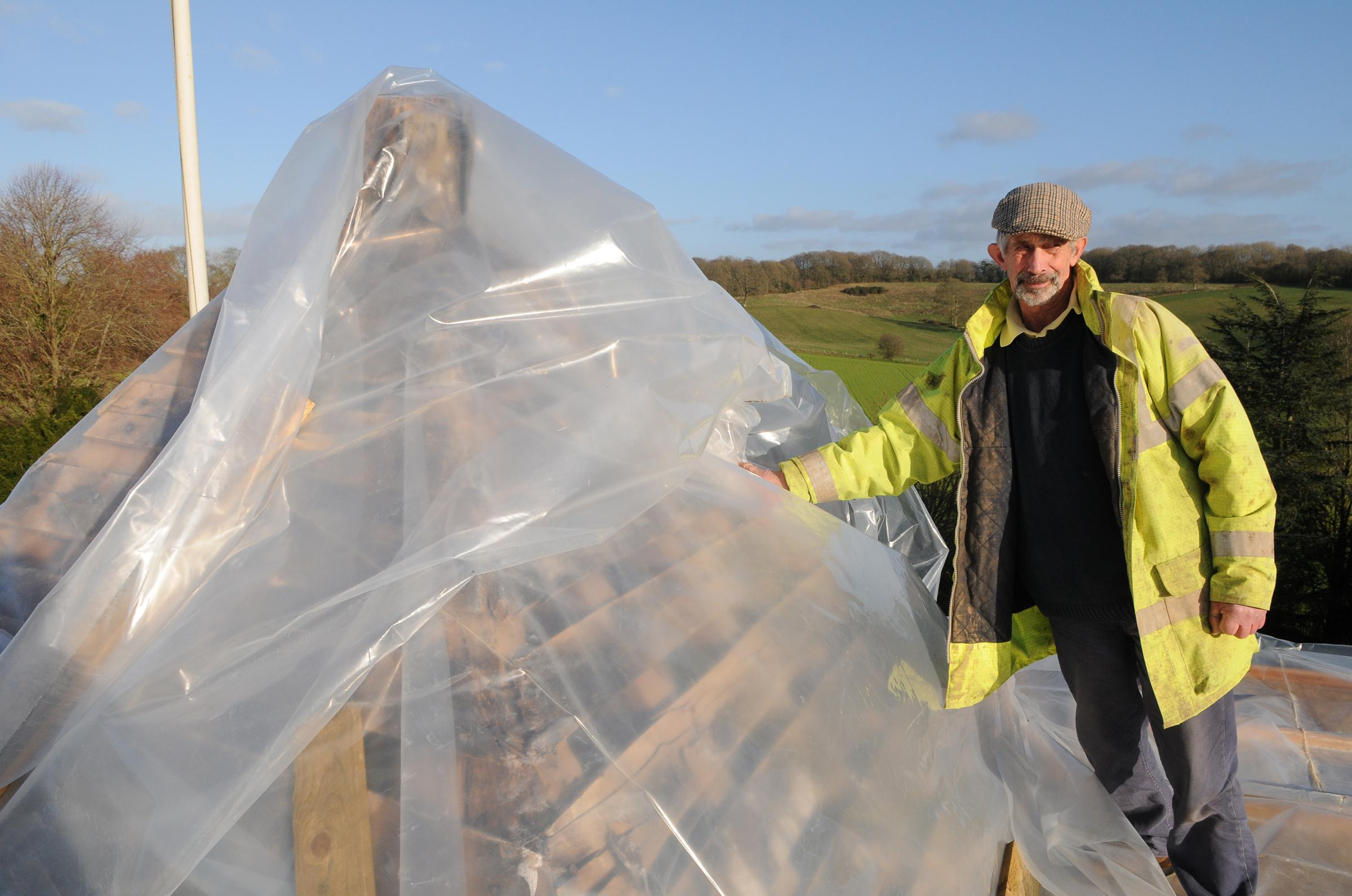 Church warden John Godber with plastic sheeting which is being used to cover the damaged roof. Picture: Tom Gregory.